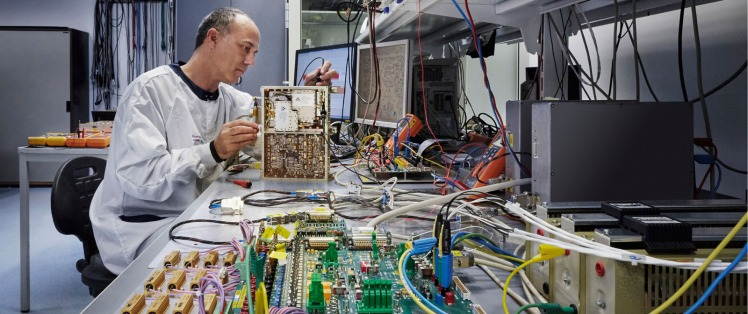 Employee working on a complex part of a space part